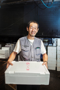 A traditional fresh fish market in Tokyo. A man holding a box of fresh fish on ice.の写真素材 [FYI02256055]