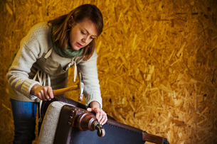 Upholstery workshop. An upholsterer using a hammer to secure fabric and padding to a chair leg.の写真素材 [FYI02256060]