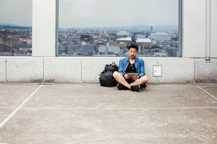 A man sitting on the floor using his smart phone, in front of a viewing point window on to a city.の写真素材 [FYI02256063]