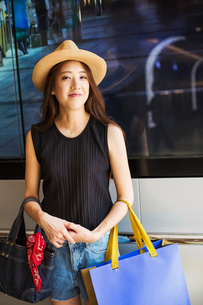 Smiling young woman with long brown hair, wearing Panama hat, holding shopping bags.の写真素材 [FYI02256079]