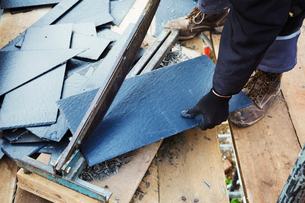 A man cutting a tile with a large guillotine blade.の写真素材 [FYI02256080]