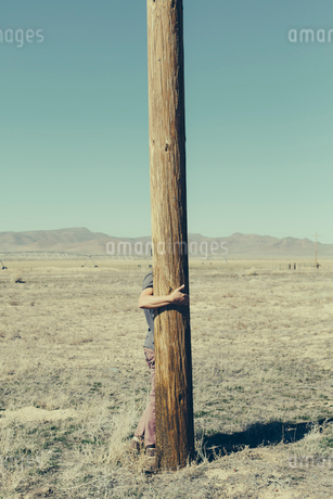 Man with his arms around a wooden utilities pole, clinging to or hugging the post in a flat open lanの写真素材 [FYI02256087]