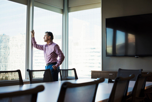 A man in a meeting room looking out of a window at an urban landscape.の写真素材 [FYI02256094]