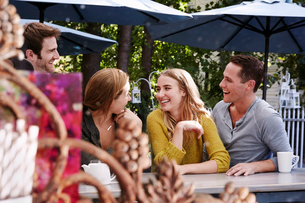 A group of people sitting at a long table in an outdoor cafe.の写真素材 [FYI02256109]