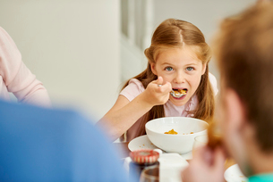 A family eating breakfast. A girl eating cereal with a spoon.の写真素材 [FYI02256129]
