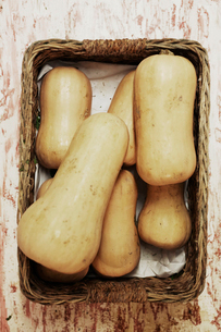 A shot of a pile of butternut squash in a basket on a wooden surface, seen from above.の写真素材 [FYI02256166]
