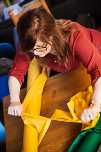 A woman ripping bright yellow fabric from a large roll on a table.の写真素材 [FYI02256170]