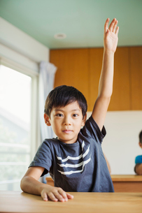 A boy with his hand up ready to answer a question.の写真素材 [FYI02256173]