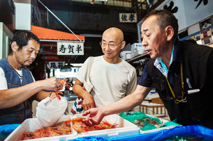 A traditional fresh fish market in Tokyo. Two people selecting shellfish for a customer to buy, fillの写真素材 [FYI02256203]