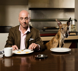 Man and brindle greyhound sitting at a table, plates with fried egg and mug.の写真素材 [FYI02256206]