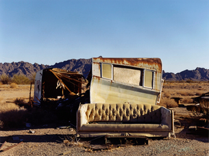 A ruined caravan, with rusting roof, a shelter, and a sofa.の写真素材 [FYI02256253]
