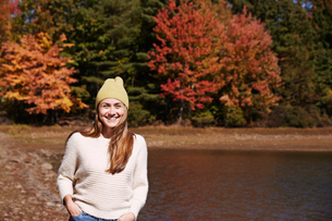 A woman in jumper and woolly hat on the lake shore in autumn.の写真素材 [FYI02256265]