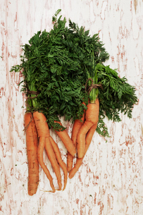 A shot of a bundle of carrots on a wooden surface, seen from above.の写真素材 [FYI02256279]