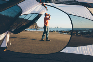 Man framed by camping tent, standing on beach and looking through binoculars at dusk, Olympic Nationの写真素材 [FYI02256293]