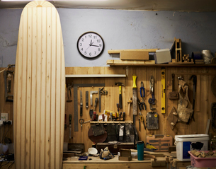 A tall wooden surfboard propped up in a workshop.の写真素材 [FYI02256295]