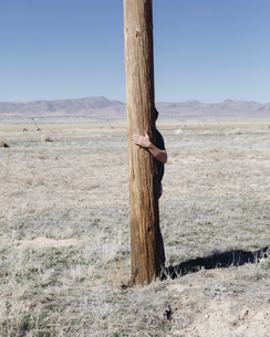 Man with his arms around a wooden utilities pole, clinging to or hugging the post in a flat open lanの写真素材 [FYI02256296]