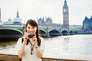 Young Japanese woman enjoying a day out in London, standing on the Queen's Walk by the River Thames.の写真素材 [FYI02256298]