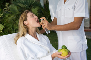 Blond woman wearing white bathrobe sitting outdoors, holding citrus fruit, a beautician spraying watの写真素材 [FYI02256316]