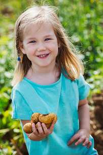 A girl holding potatoes in a vegetable patch.の写真素材 [FYI02256318]