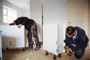 Two builders, building white kitchen units.の写真素材 [FYI02256325]