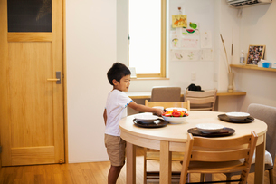 Family home. A boy setting the table for a meal.の写真素材 [FYI02256329]