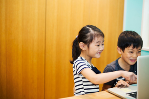 Two children sharing a laptop computer.の写真素材 [FYI02256336]