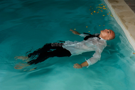 Man wearing trousers, shorts and tie floating on his back in swimming pool.の写真素材 [FYI02256340]