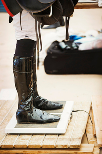 Rider wearing shiny black riding boots at the weigh in  on weighing scale, holding a saddle, beforeの写真素材 [FYI02256359]