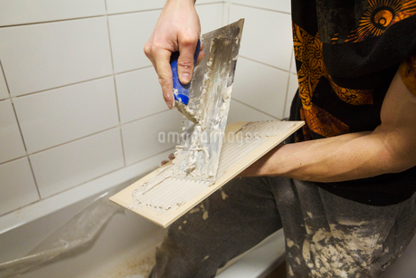 Close up of a builder, tiler spreading adhesive on the back a tile.の写真素材 [FYI02256363]
