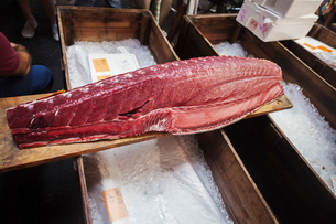 A traditional fresh fish market in Tokyo. A large fillet of tuna on a wooden board.の写真素材 [FYI02256372]