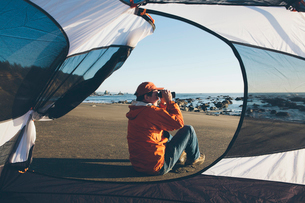 Man framed by camping tent, sitting on beach and looking through binoculars at dusk, Olympic Nationaの写真素材 [FYI02256385]
