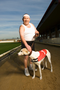 Man in sportswear standing on a racetrack, holding a white greyhound wearing red bib with number oneの写真素材 [FYI02256390]