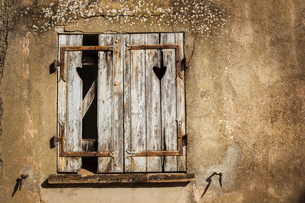 A house with cracked plaster, with broken wooden shutters.の写真素材 [FYI02256419]