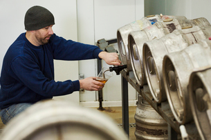 Man drawing some beer from a metal keg in a brewery for testing.の写真素材 [FYI02256426]