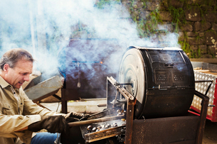 A man roasting chestnuts over hot coals in a large drum, raking out the roasted nuts.の写真素材 [FYI02256433]