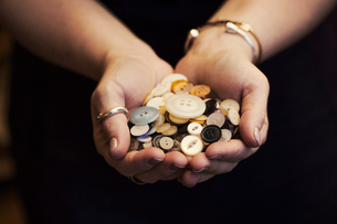 A woman holding hands full of buttons of varied shape, size and colour.の写真素材 [FYI02256452]