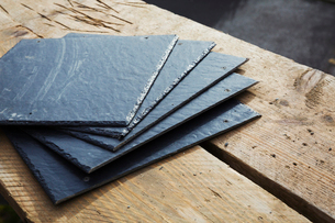 A pile of slate tiles on a wooden surface.の写真素材 [FYI02256470]