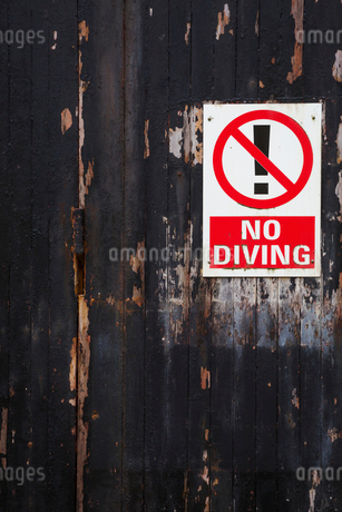 Close up of a 'No Diving' sign on a weathered wooden wall.の写真素材 [FYI02256473]