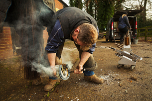 A farrier shoeing a horse, bending down and fitting a new horseshoe to a horse's hoof.の写真素材 [FYI02256476]