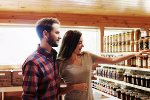 A young man and woman choosing from a display of canned produce in a farm shop.の写真素材 [FYI02256481]