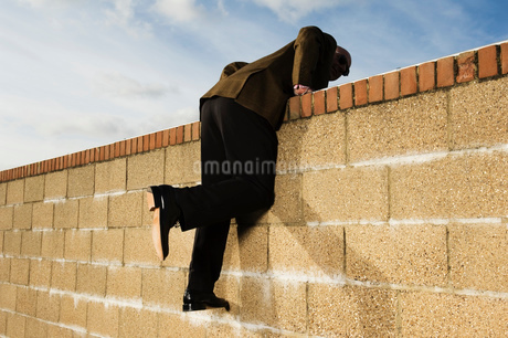 Side view of man wearing a suit climbing over yellow brick wall.の写真素材 [FYI02256518]