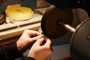 A person holding a small ring and using a grinding machine to shape and polish it. Workbench in a jeの写真素材 [FYI02256519]