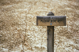 Cracked parched soil surface of the desert, and a Please Stay Off sign on the surface of the desertの写真素材 [FYI02256528]