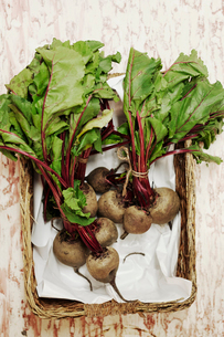 A shot of bundles of beets in a basket on a wooden surface, seen from above.の写真素材 [FYI02256537]