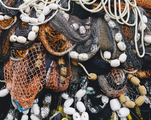 Close up of a pile of tangled up commercial fishing nets with floats attached.の写真素材 [FYI02256550]