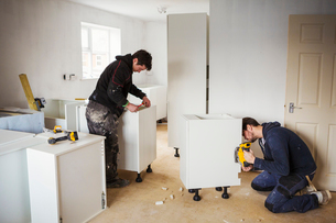 Two builders, building white kitchen units.の写真素材 [FYI02256623]