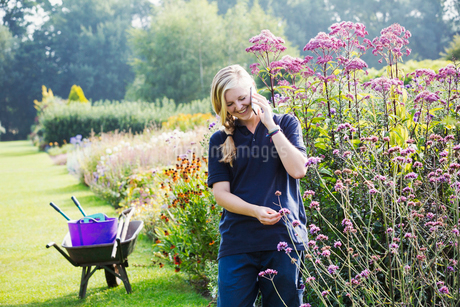Female gardener at Waterperry Gardens in Oxfordshire, using a mobile phone.の写真素材 [FYI02256626]