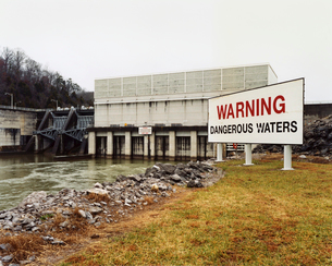 Warning signs by a water channel, Dangerous Waters. A covered bridge, water flow management barrier.の写真素材 [FYI02256660]