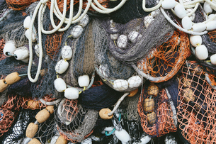 Close up of a pile of tangled up commercial fishing nets with floats attached.の写真素材 [FYI02256678]