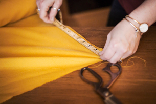 A woman using a tape measure to measure yellow fabric for cutting out.の写真素材 [FYI02256686]